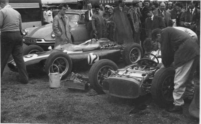 1961 GP de Gran Bretaña Paddock - Bruce McLaren y 'Noddy' ajustando el monoplaza - Cooper-Climax T54 'Cooper Car Company'